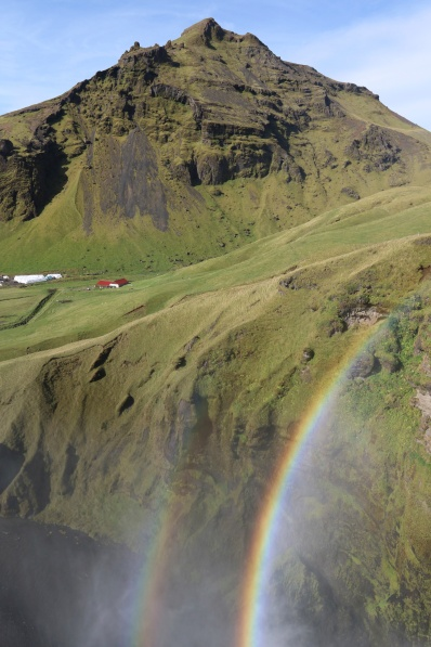 Waterfall spray spreads out over an idyllic Icelandic valley.